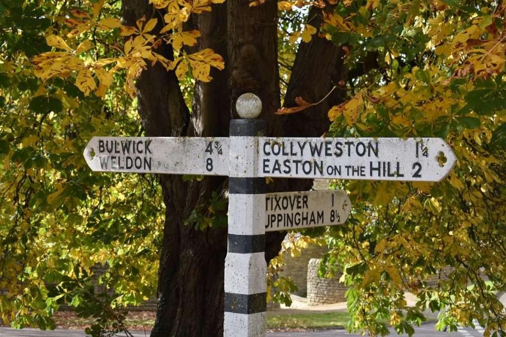 Signpost to places near Duddington under horsechestut in early autumn