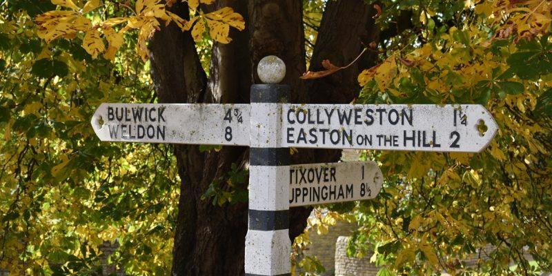 Signpost to places near Duddington under horsechestut in early autumn